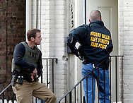 An FBI agent (left) and a Hudson Valley Safe Streets Task Force officer (right) serve a search warrant at 113 Lander Street in the City of Newburgh, NY on Thursday morning, May 13, 2010. Multiple law enforcement agencies raided gang hideouts and made arrests of Bloods and Latin Kings street gang members at various locations throughout the city.