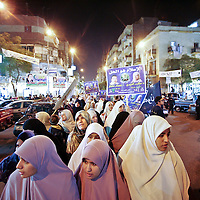 Egyptian women hold a poster of Makarem el-Dairi, left, a 55-year old widow and holder of a PH.D. in Arabic literature and a member of the Muslim Brotherhood who is running as an independent for a seat in parliament, during a march in Cairo. Makarem has just become the only woman in Egypt's election campaign to run under the banner of the Muslim Brotherhood, the banned group that says woman's place is first and foremost in the home. November 2005.