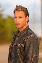 sexy man in a leather jacket at sunset