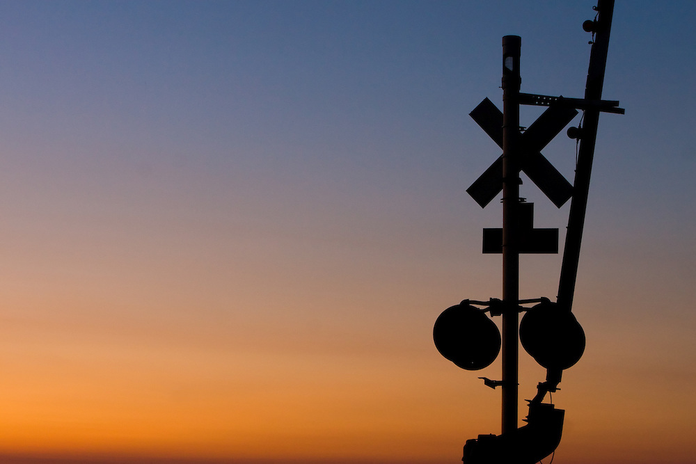 Silhouetted against a colorful sunset, a railroad crossing gate stands motionless.