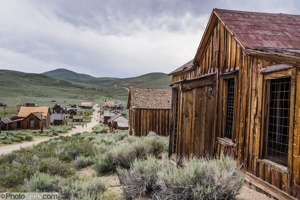 """Ramshackle houses line Green Street in Bodie, California's official state gold rush ghost town. Bodie State Historic Park lies in the Bodie Hills east of the Sierra Nevada mountain range in Mono County, near Bridgeport, California, USA. After W. S. Bodey's original gold discovery in 1859, profitable gold ore discoveries in 1876 and 1878 transformed """"Bodie"""" from an isolated mining camp to a Wild West boomtown. By 1879, Bodie had a population of 5000-7000 people with 2000 buildings. At its peak, 65 saloons lined Main Street, which was a mile long. Bodie declined rapidly 1912-1917 and the last mine closed in 1942. Bodie became a National Historic Landmark in 1961 and Bodie State Historic Park in 1962."""