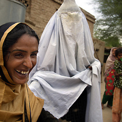 Mukhtar Mai, 33, is teased by a family member wearing a burqa, which Mai now refuses to wear, Meerwala, Pakistan, April 28, 2005.<br />Mai, is visiting with an aunt she hadn't seen for four years. She went against the Pakistani tradition of committing suicide when she brought charges against the men who gang raped her nearly three years ago.