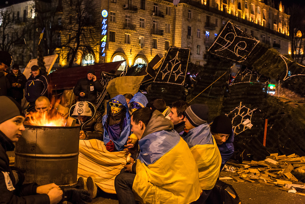 KIEV, UKRAINE - DECEMBER 3: Protesters warm themselves by a fire during ongoing anti-government protests in Independence Square on December 3, 2013 in Kiev, Ukraine. Thousands of people have been protesting against the government since a decision by Ukrainian president Viktor Yanukovych to suspend a trade and partnership agreement with the European Union in favor of incentives from Russia. (Photo by Brendan Hoffman/Getty Images) *** Local Caption ***