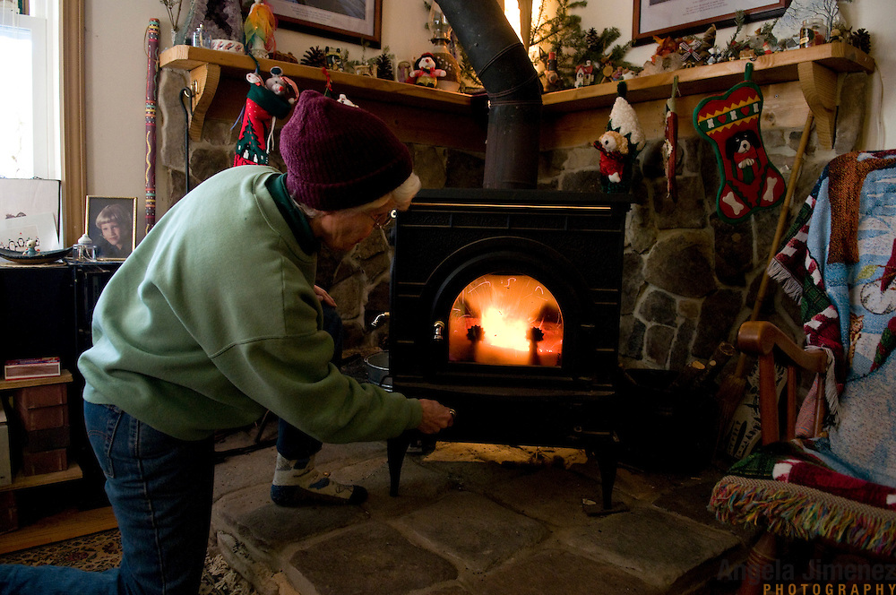 """Date: 1/08/09.Desk: STL.Slug: WOMYN.Assign ID: 30074969A..Emily Greene, 62, lights the wood-burning fireplace at her home at Alapine, a """"womyn's land"""" or lesbian intentional community, in rural northeast Alabama. ..(*the exact town/location of the community cannot be revealed in the caption or article, per agreement with the subjects)..Photo by Angela Jimenez for The New York Times .photographer contact 917-586-0916"""