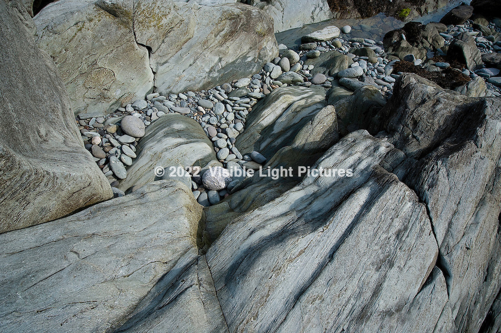 Rocks and stones on the beach at low tide. Rocky beach along the Sachuest Point National Wildlife Refuge
