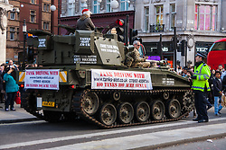 """London, December 20th 2014. Tens of thousands of shoppers descend on central London to scoop up pre-Christmas bargains as retailers offer discount incentives on """"Panic Saturday"""". PICTURED: A policeman talks with a tank driver on Regents Street."""