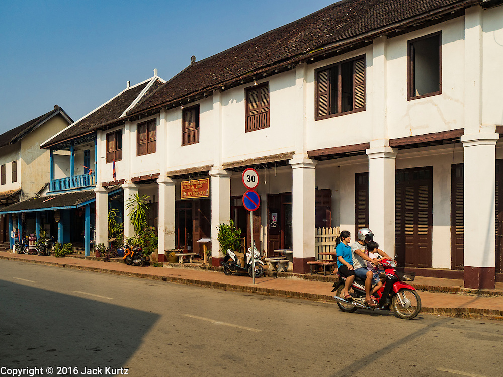 """13 MARCH 2016 - LUANG PRABANG, LAOS:  A Lao family on a motorcycle rides past a French colonial house that has been turned into a spa in Luang Prabang. Luang Prabang was named a UNESCO World Heritage Site in 1995. The move saved the city's colonial architecture but the explosion of mass tourism has taken a toll on the city's soul. According to one recent study, a small plot of land that sold for $8,000 three years ago now goes for $120,000. Many longtime residents are selling their homes and moving to small developments around the city. The old homes are then converted to guesthouses, restaurants and spas. The city is famous for the morning """"tak bat,"""" or monks' morning alms rounds. Every morning hundreds of Buddhist monks come out before dawn and walk in a silent procession through the city accepting alms from residents. Now, most of the people presenting alms to the monks are tourists, since so many Lao people have moved outside of the city center. About 50,000 people are thought to live in the Luang Prabang area, the city received more than 530,000 tourists in 2014.   PHOTO BY JACK KURTZ"""