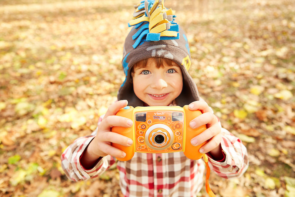 Lifestyle image of kid wearing hat with orange toy camera in park with autumn leaves on ground in background