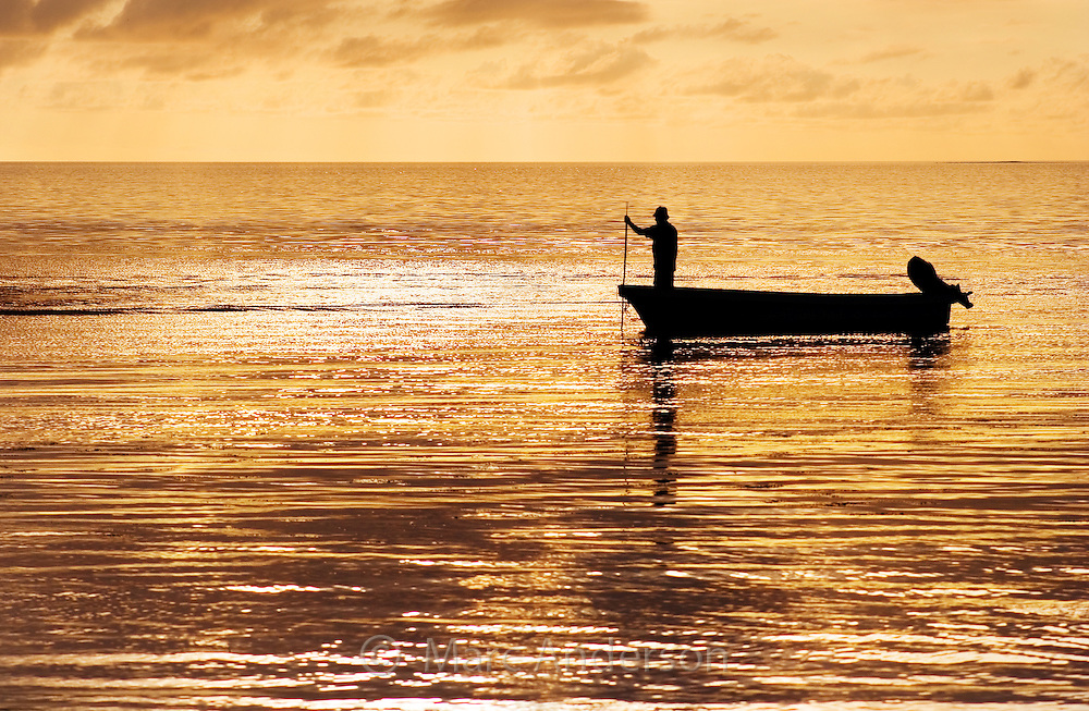 Silhouette of an indigenous Fijian man on a small fishing boat at sunset.