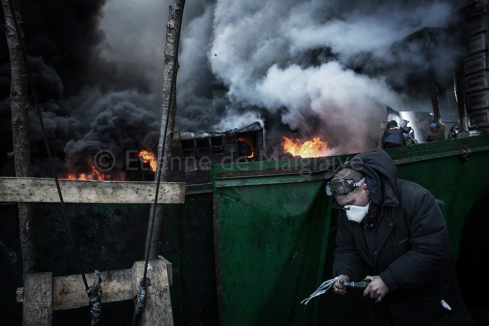 Standoff between antigovernment protesters and riot police on Hrushevskoho street near Maidan Square in Kiev. Protesters maintain the barricade ablaze with tires and cocktail Molotov as riot police stands by on the other side, trying to douse the flames with water hoses. 23 January 2014.