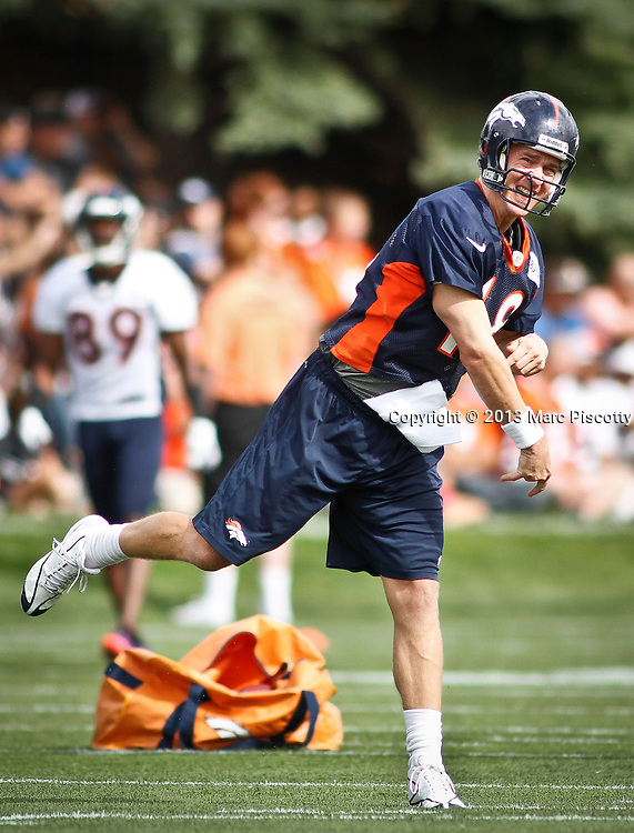 SHOT 7/25/13 9:31:53 AM - Denver Broncos quarterback Peyton Manning #18 throws a deep pass as he runs through drills during opening day of the team's training camp July 25, 2013 at Dove Valley in Englewood, Co.  (Photo by Marc Piscotty / © 2013)