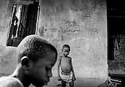 The walls in Mandopulahun are covered with drawings of soldiers shooting unarmed civilians. The drawings are at adult height and derive from Sierra Leone's own civil war. Now the village houses refugees from another West African war. June 2002.