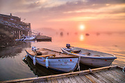 Two work boats rest against the dock at Five Islands as the sun rises through the fog and mist across the bay.