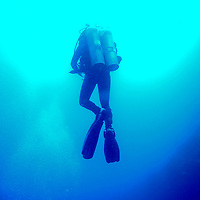 """A scuba diver ascends inside the Blue Hole in Dahab, Egypt. The Blue Hole is notorious for the number of diving fatalities which have occurred there, earning it the sobriquet """"World's Most Dangerous Dive Site"""" and the nickname """"Diver's Cemetery"""". The site is signposted by a sign that says """"Blue hole: Easy entry"""". Accidents are frequently caused when divers attempt to find the tunnel through the reef (known as """"The Arch"""") connecting the Blue Hole and open water at about 52 m depth. According to dive experts roughly 10 people die each year. April 2012."""