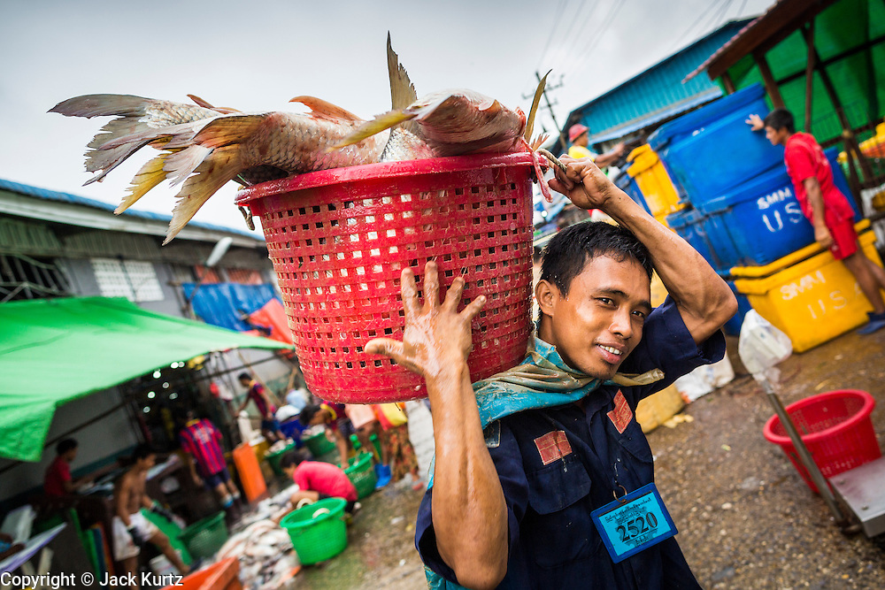 09 JUNE 2014 - YANGON, MYANMAR: A laborer brings a basket of fresh fish to a truck in the San Pya Fish Market (also spelled Sanpya). San Pya Fish Market in Yangon is one of the largest wholesale fish markets in Yangon. The market is busiest in early in the morning, from before dawn until about 10AM.    PHOTO BY JACK KURTZ