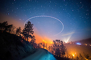 The Shirley Fire burns at night off of Old State Rd near Lake Isabella, CA. An Air Attack plane flies overhead in a circular pattern, creating a perfect circle. <br /> <br /> Long exposure image. <br /> <br /> The Shirley Fire burns overnight near Lake Isabella, CA on the evening of June 15, 2014. By morning the fire had burned 2200 acres and was 10% contained. At least two structures were lost.<br /> <br /> Date 20140615<br /> <br /> Date 20140615