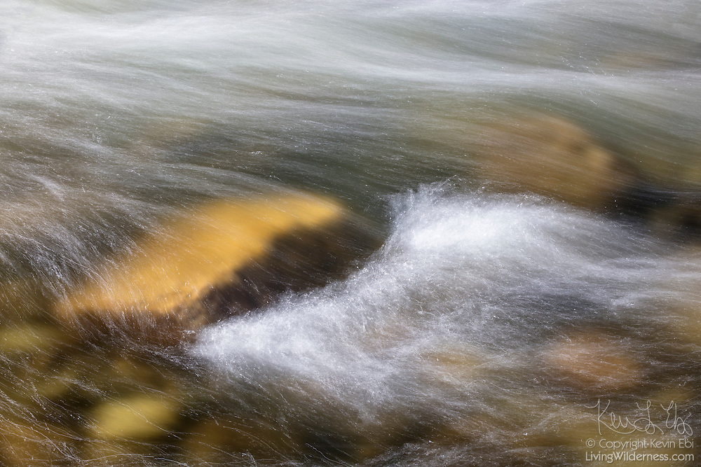 The Merced River, swollen after a period of exceptionally heavy rain, flows over river rocks in Yosemite National Park, California.