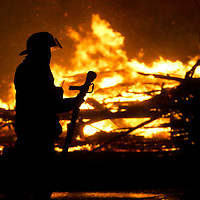 A firefighter with a fire nozzle watches helplessly as a block of burning buildings in downtown Galveston, Texas September 23, 2005 are completely engulfed. Hurricane force winds threw burning embers everywhere as Hurricane Rita approached only hours away.