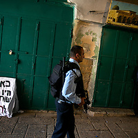 An Israeli police officer patrol next to a sign saying &quot; Here  (sellers) were involved in the murder&quot; outside of closed Palestinian shops  where a stabbing attack took place in Jerusalem's Old City, Sunday, Oct.8, 2015. <br /> Photo by Olivier Fitoussi.