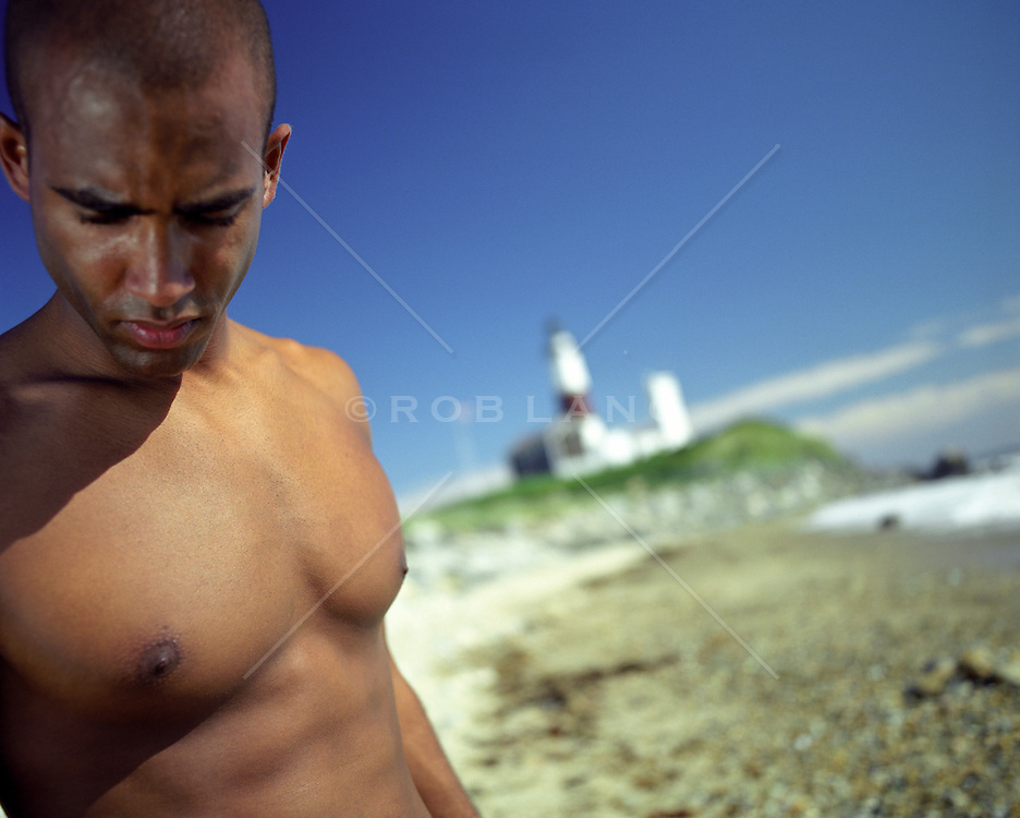 shirtless man looking at the beach near the Montauk Lighthouse