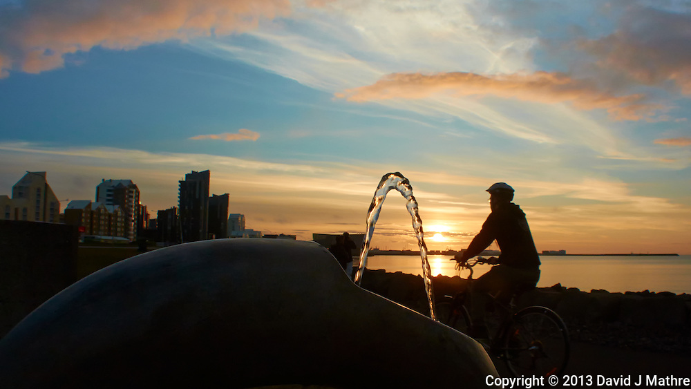 Sunset Along the Reykjavik Harbor Walkway. Image taken with a Nikon 1 V2 camera and 10 mm f/2.8 lens (ISO 160, 10 mm, f/8, 1/400 sec). The foreground is a water fountain, and the bicycle rider just happened to go by as I took the image. Nikonians Academy Iceland Photo Adventure Trip.