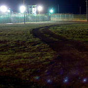 "A night view of a dirt road which snakes its way toward the Camp Delta detention facility in Guantanamo Bay. The U.S. Government is currently holding approximately 340 ""enemy combatants"" in Guantanamo Bay, Cuba. They were captured during the ""Global War on Terrorism"" after the attacks on the United States on September 11, 2001. This photo was reviewed by a U.S. Military official before transmission."