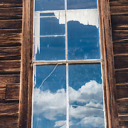 """An old window reflects cumulus clouds at Bodie, California's official state gold rush ghost town. Bodie State Historic Park lies in the Bodie Hills east of the Sierra Nevada mountain range in Mono County, near Bridgeport, California, USA. After W. S. Bodey's original gold discovery in 1859, profitable gold ore discoveries in 1876 and 1878 transformed """"Bodie"""" from an isolated mining camp to a Wild West boomtown. By 1879, Bodie had a population of 5000-7000 people with 2000 buildings. At its peak, 65 saloons lined Main Street, which was a mile long. Bodie declined rapidly 1912-1917 and the last mine closed in 1942. Bodie became a National Historic Landmark in 1961 and Bodie State Historic Park in 1962."""