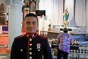 Portrait of a young Marine fresh out of boot camp on home leave. He was back in Saipan to visit mom, who is in the background lighting a candle for him at church at the 0600 mass. The Marines are revered by many older folks on Saipan, as they liberated the island from the Japanese in a fierce battle in WWII, and saved many lives.