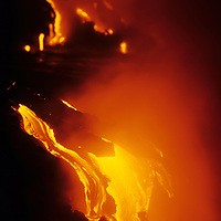 USA, Hawaii, Volcanoes National Park,  Stream of molten lava from Kilauea pours into ocean at night