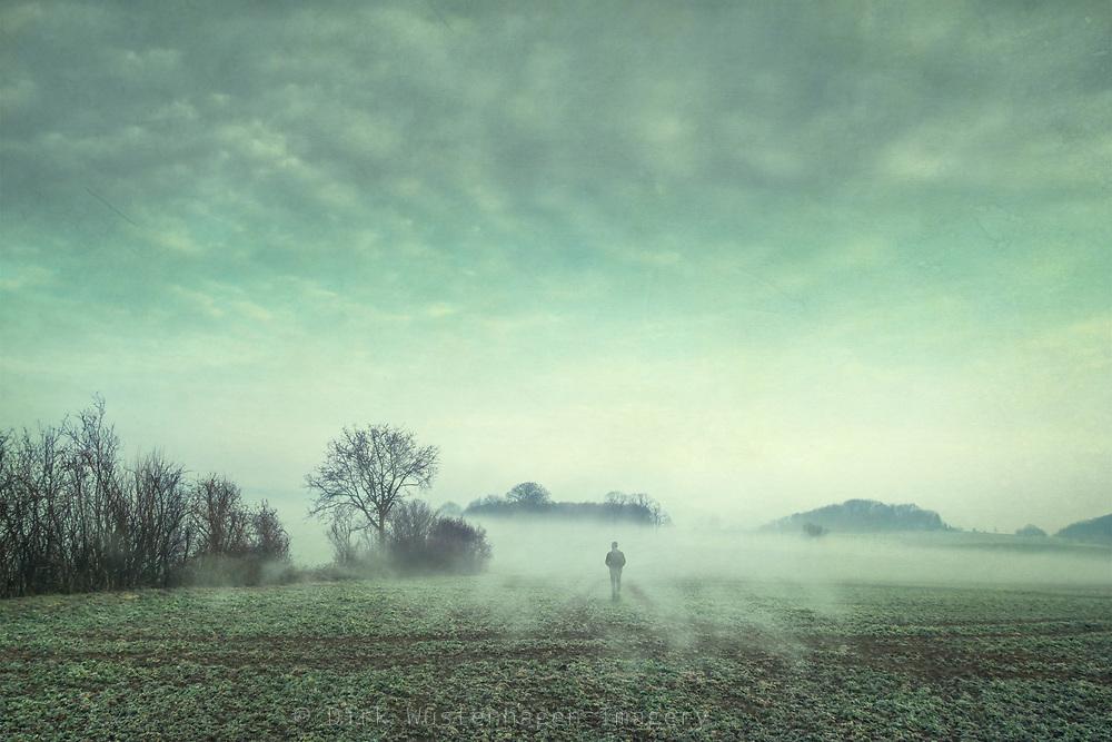 Man walking over a misty field