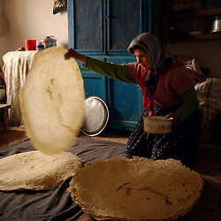 Ali Ipak 's wife Ayse prepares a type of bread by sprinkling it with water and warming it as she prepares lunch December 12, 2005 in central Turkey, Konya in Kutoren district, about 400 kilometers from Ankara.  (Ami Vitale)