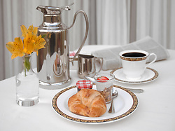Continental breakfast with a croissant, yogurt and coffee on a white linen tablecloth
