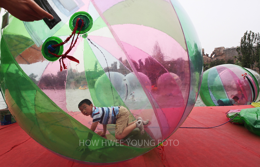 epa02182203 A Chinese boy play in a giant water balloon in an amusement park on Children's Day in Beijing, China, 01 June 2010. China celebrates Children's Day amid security concerns as several kindergartens and schools in the national capital held back on celebrations, after a string of school stabbings around the country claiming 17 lives and injuring more than 50 earlier this year.  EPA/HOW HWEE YOUNG