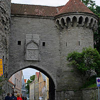 Europe, Estonia, Tallinn. Visitors approach an archway in the historic walls and towers of Tallinn.