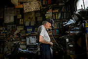 """Angelo """"Tubby"""" Galzarano, 79, speaks to a customer on the phone in his repair shop, Tubby's Auto Service, in West Aliquippa, Pennsylvania, USA on June 5, 2015. Galzarano has worked and lived in West Aliquippa his entire life."""
