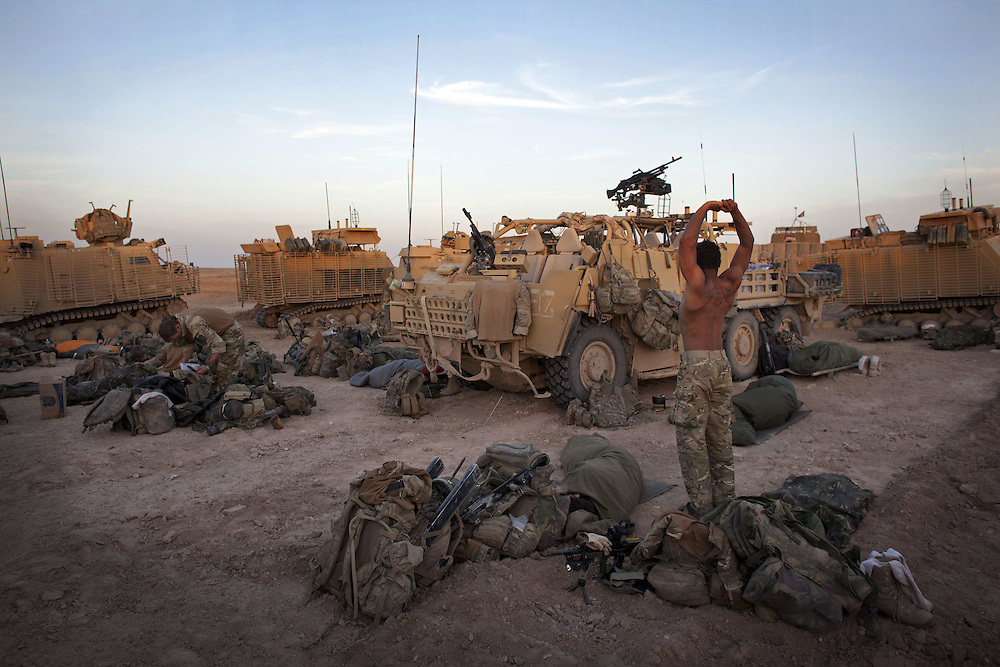 British soldiers of 16 Air Assault Bde's elite BRF (Brigade Reconnaissance Force) start a new day after spending the night sleeping in the desert within a defensive perimeter formed by their convoy of Warthog and Jackal armored fighting vehicles after an operation in the village of Kakaran in Helmand Province, Southern Afghanistan on the 15th of March 2011.