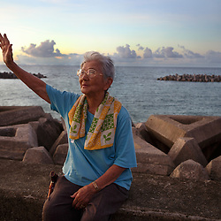 Masako Taira, 90, waves as the sun sets in Ogimi, Okinawa.
