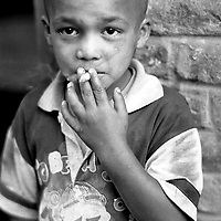 An orphan child smokes a cigarette to show off his attitude.
