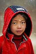 Bhutanese child in falling snow in Gangtey, Bhutan. Digitally Manipulated Image. Stylised by sharpening and enhancing color