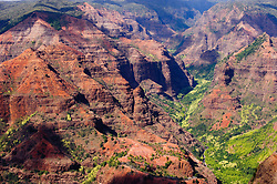 Waimea Canyon on the west side of the island of Kauai in Hawaii is a large canyon, approximately ten miles long and up to 3,000 feet deep. It is the largest canyon in the Pacific. The canyon, located in Waimea Canyon State Park and near Kokee State Park, was formed by the Waimea River which gets much of its water from the heavy rainfall on Mount Waialeale one of the wettest places on earth. This erosion was aided by a catastrophic collapse of the volcano that created Kauai, the oldest of the main Hawaiian islands. Over time, exposed basalt has weathered from its original black to bright red. The canyon can be seen from several overlooks on the road from Waimea to Kokee State Park.