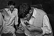 Two young Pashtun men smoke heroin inthe entrace to their home in Peshawar..Record opium crops in neighbouring Afghanistan have resulted in a cheap, affordable and plentiful supply of heroin and opium in Pakistan...In the frontier town of Peshawar, a gram of heroin sells for 100 rupees, little more than a dollar. Most addicts smoke or ?chase the dragon?, some inject but the inaccessibility of syringes dictate most addicts smoke the drug...Opium can be found in its pure form, fresh from record harvests in Afghanistan. Most is processed into heroin in the many factories along the Afghan / Pakistan borer, but some is retained, especially in the tribal province, for ?traditional medicinal? purposes such as bile din tea for curing arthritis and flu symptoms....