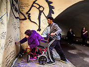 21 APRIL 2017 - CHANHASSEN, MN: FELIZ KEDINEOGLU, (left) from Los Angeles, writes a note to Prince in the pedestrian tunnel in front of Paisley Park, his former home and recording studio. ROB LOVE, from Memphis, TN, was holding her wheelchair so she could write the note. The tunnel has become a memorial to Prince, people have drawn graffiti in the tunnel honoring him and they leave memorials in the tunnel. The superstar died from an accidental overdose of the opioid fentanyl on April 21, 2016. Friday was the first anniversary of his death. Crowds of people gathered at Paisley Park, which is now a museum, to honor the Minnesota born musician.     PHOTO BY JACK KURTZ