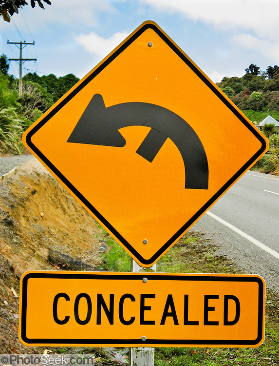 Funny sign: Concealed drive sign with black arrow on yellow-orange background, on a highway in New Zealand.