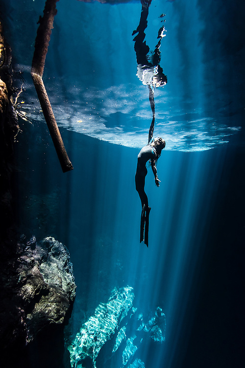 México, Quintana Roo. A freediver champion surfaces among the searays and meets with her reflection at cenote the Pit.