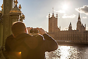 A man takes a photo of the Houses of Parliament on an iPhone, before sunset