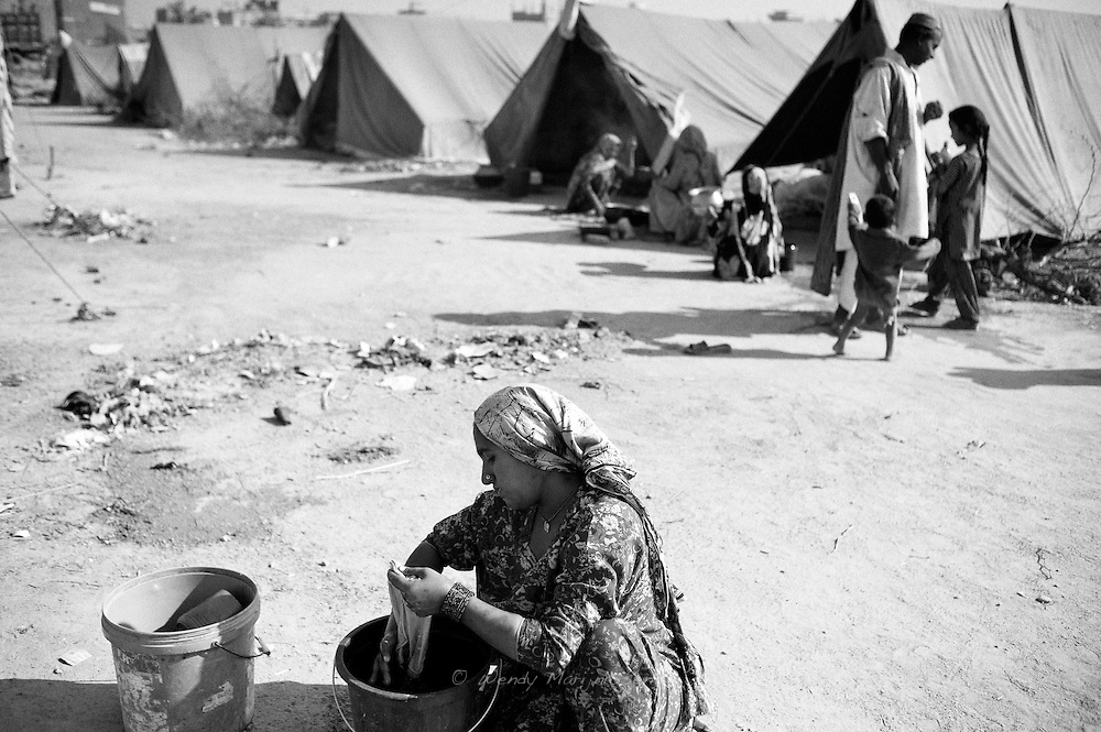 Hamida washed clothes and cloths outside her tent. Already a day after giving birth, Hamida returned to the camp, and slipped back into her role of care taker of her children with no time to recover physically after her delivery. Karachi, Pakistan, 2010