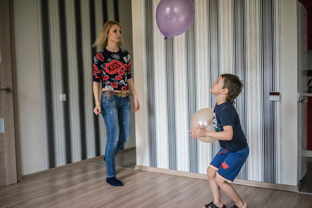 Olga Kirichuk, 29, watches her son Yaroslav, 6, play with balloons on Tuesday, April 28, 2015 in Lviv, Ukraine. After her husband joined forces with pro-Russian rebels in eastern Ukraine, she left him and other members of her family with anti-Ukrainian views and took her son to Lviv, where they live with a friend. CREDIT: Brendan Hoffman/Prime for the Wall Street Journal UKRMIGRATION