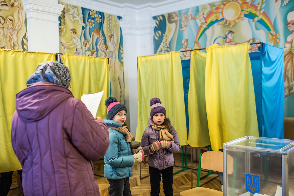 KIEV, UKRAINE - OCTOBER 26: Two girls wait as their mother fills out her ballot in parliamentary elections at a polling station on October 26, 2014 in Kiev, Ukraine. Although a low turnout is expected in the east of the country amid continued fighting between Ukrainian forces and pro-Russian separatists, Ukraine is expected to elect a pro-Western parliament in a further move away from Russian influence. (Photo by Brendan Hoffman/Getty Images) *** Local Caption ***