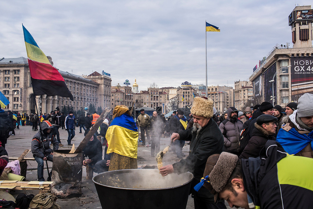 A man serves soup to anti-government protesters in Independence Square, part of an extensive effort to feed and keep warm the thousands of people occupying the square and nearby buildings.