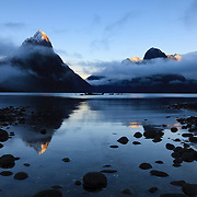 Mitre Peak, Mount Pembroke, and other mountains in Fiordland National Park, New Zealand, are reflected in Milford Sound during a foggy sunrise.